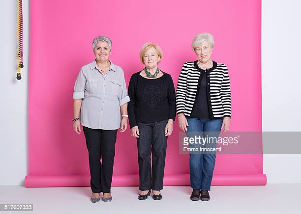 group of mature friends smiling in pink studio