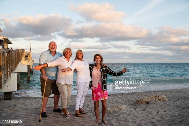 """group of mature lgbtq friends in posing on the beach. - """"martine doucet"""" or martinedoucet stock pictures, royalty-free photos & images"""