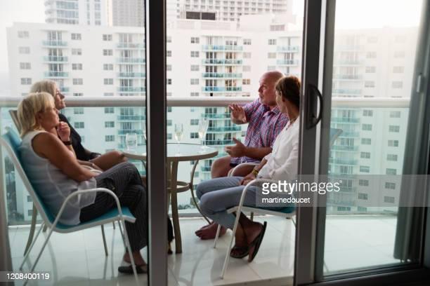 """grupo de amigos lgbtq maduros en un balcón sobre el océano. - """"martine doucet"""" or martinedoucet fotografías e imágenes de stock"""