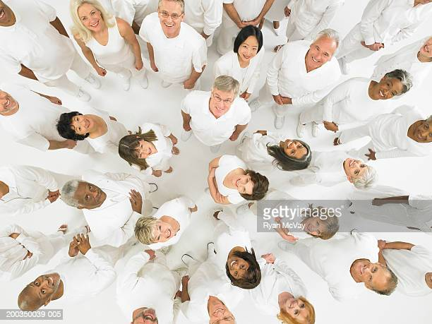 Group of mature men and women wearing white, looking up