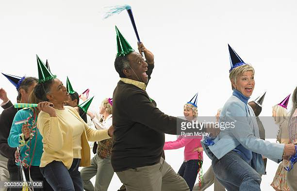 Group of mature men and women with party accessories, dancing