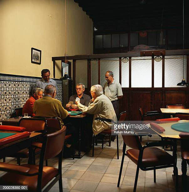 Group of mature men playing cards in bar