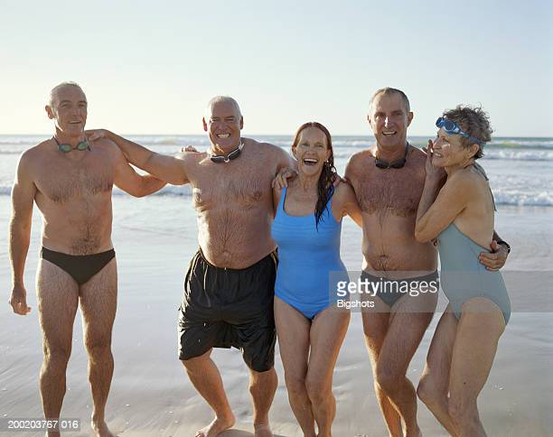 group of mature people on beach, arms around each other in line - man wearing speedo stock photos and pictures