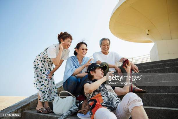 a group of mature people taking a selfie - アクティブシニア ストックフォトと画像