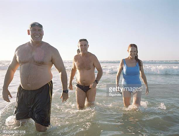 group of mature people walking out of sea, smiling - man wearing speedo stock photos and pictures