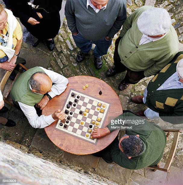 group of mature people watching two men playing chess, overhead view - only mature men stock pictures, royalty-free photos & images