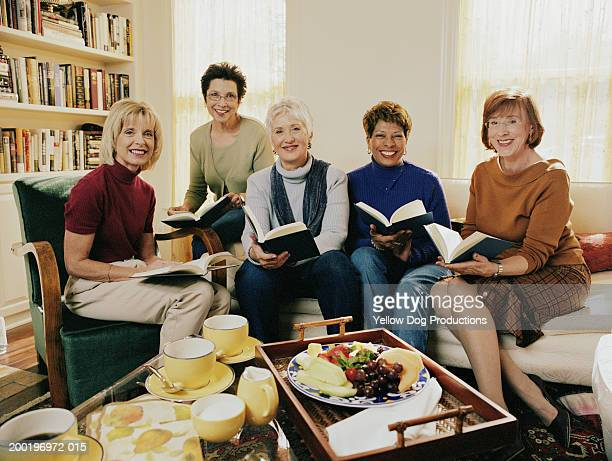 Group of mature women in living room holding books smiling, portrait