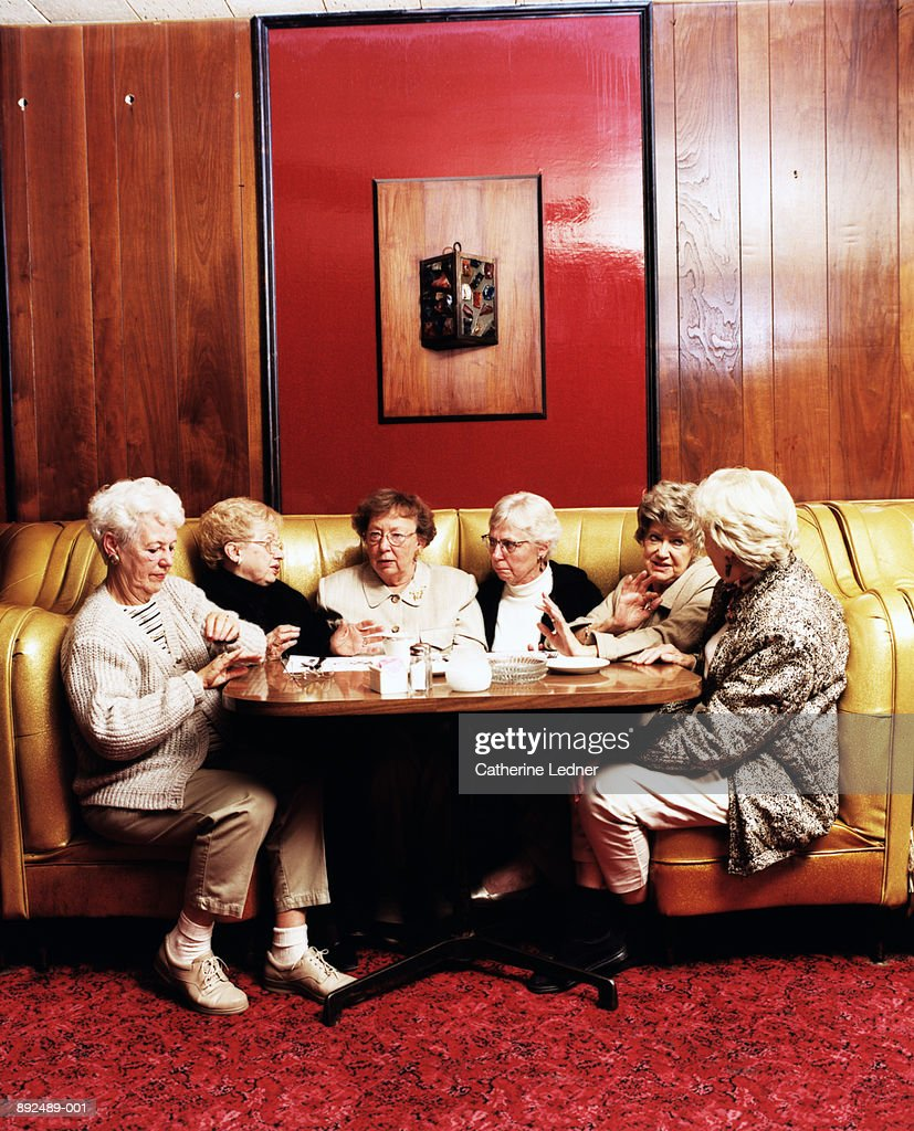Group of mature women talking in restaurant booth : Stock-Foto