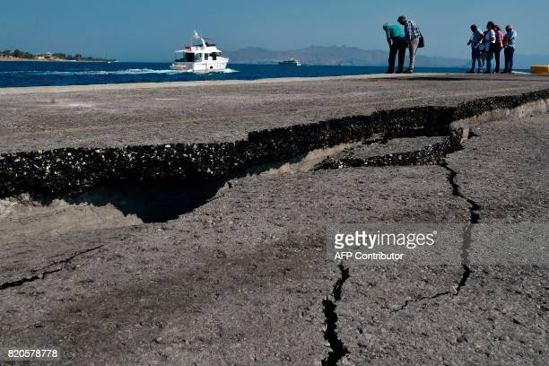 A group of mechanics look at damages at the main port of the Kos island on July 22 2017 following a 65 magnitude earthquake which struck the region...