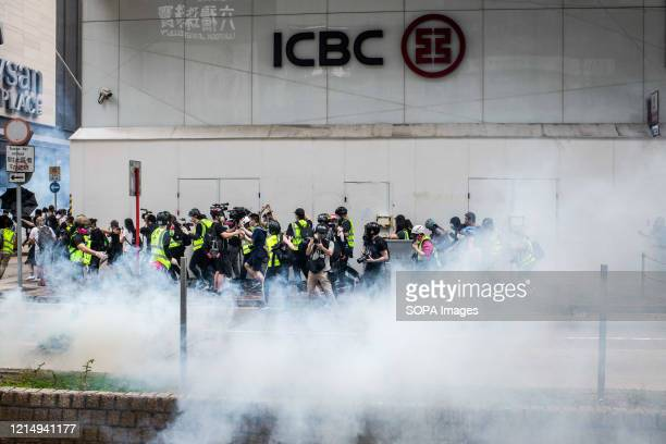A group of media professionals behind a cloud of teargas during demonstrations against the draft bill Hong Kong police fired teargas and pepper spray...