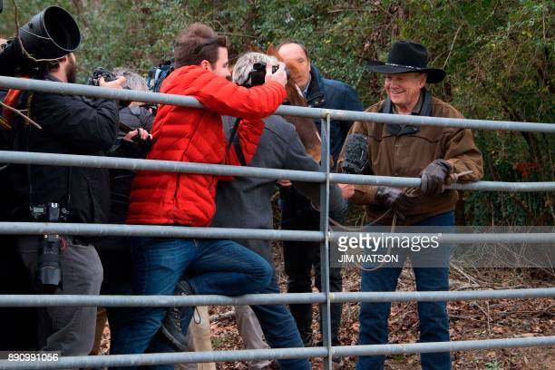 A group of media try to get to Republican Senatorial candidate Roy Moore as he ties up his horse Sassy near the polling station before voting in...