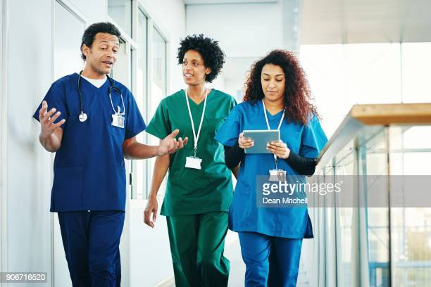 group of medical professionals discussing along hospital corridor - medical occupation stock pictures, royalty-free photos & images