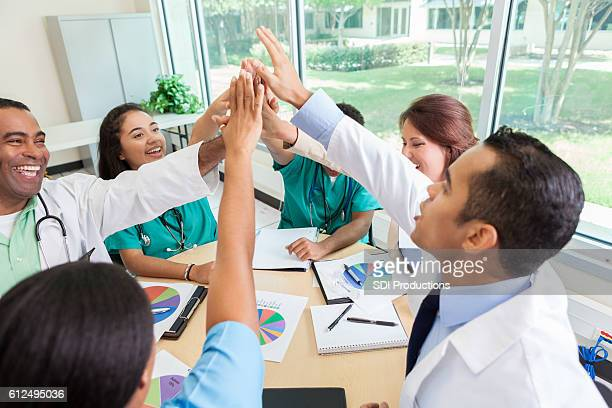 Group of medical professionals put their hands together during meeting