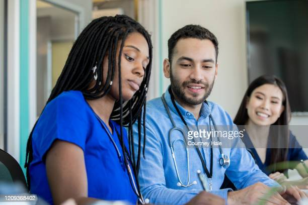 group of medical professionals sitting at a conference table - civilian stock pictures, royalty-free photos & images