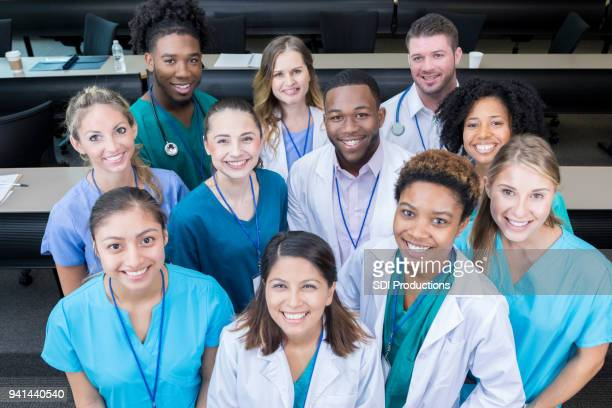group of medical students smile for camera - group of doctors stock pictures, royalty-free photos & images