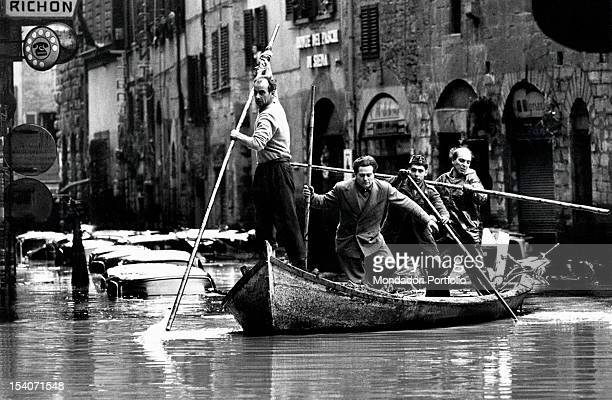 A group of men aboard a boat in the historic center of Florence during the flood of 1966 Italy