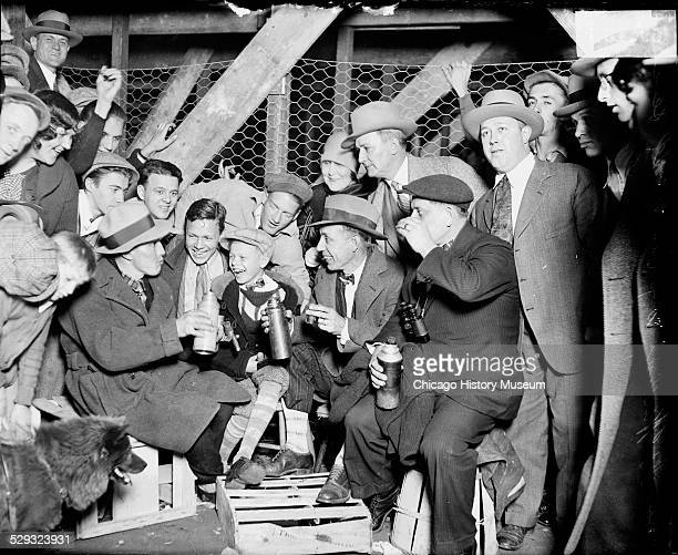 Group of men and a boy sitting on crates outside Wrigley Field waiting to enter the ballpark for a 1929 World Series game between the National...
