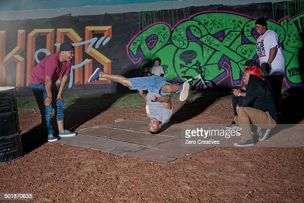 Group of men and boys breakdancing in park at night