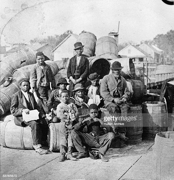 Group of men and boys, presumably slaves, sit on and around a pile of barrels on a pier or dock, Jacksonville, Florida, mid 19th Century.