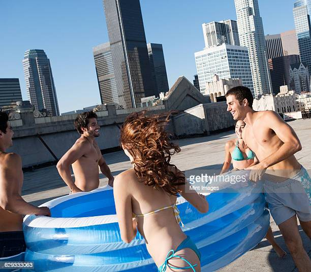 A group of men and women carrying a small inflatable water pool on to a city rooftop