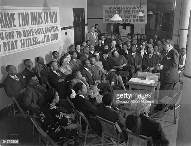 A group of men and women gather at the Parkway Community House to discuss labor and civil rights issues during World War II Chicago IL ca1945