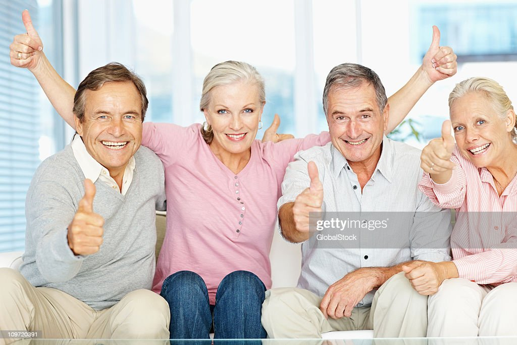 Group of men and women gesturing thumbs up sign : Stock Photo