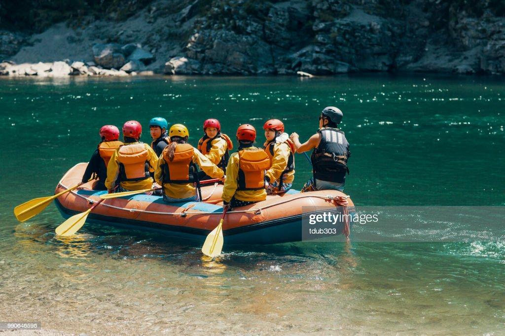 Grupp män och kvinnor i en flotte på en flod : Bildbanksbilder