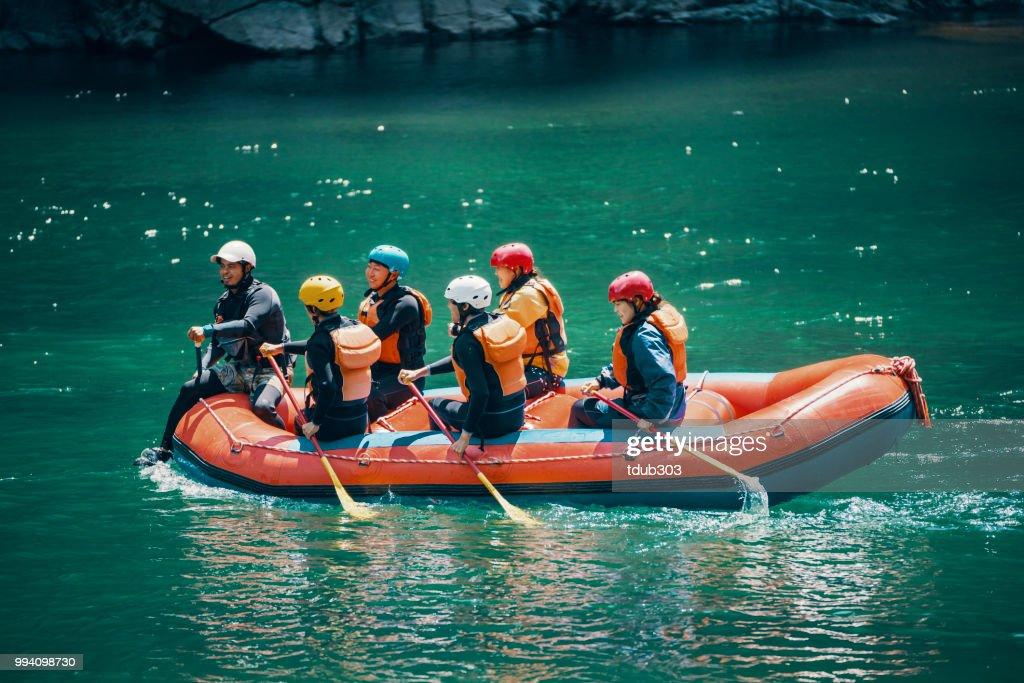 Group of men and women in a raft on a river : Foto de stock