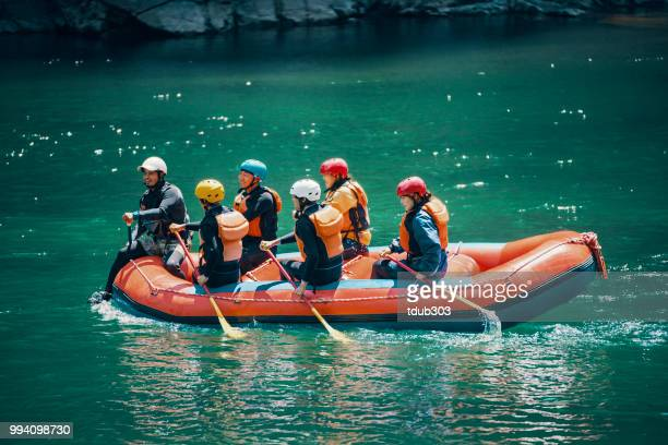 Gruppe von Männern und Frauen in einem Floß auf einem Fluss