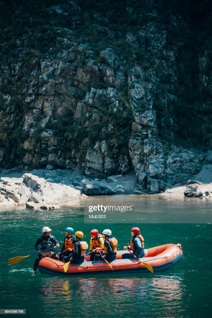 Group of men and women in a raft on a river : Foto stock