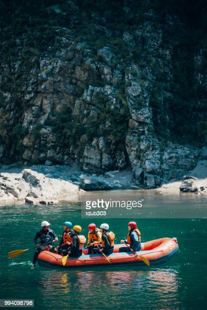 Groep van mannen en vrouwen in een vlot aan een rivier