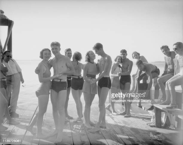 Group of men and women modeling bathing suits that have been approved by the police chief on the Alpha Chi Omega pier on Lake Mendota Madison...