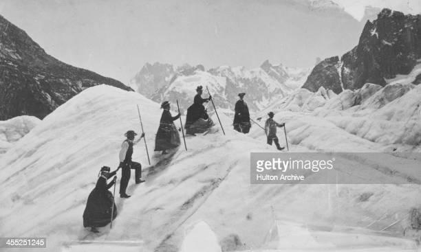 A group of men and women mountain climbing on the Mer de Glace France circa 1870