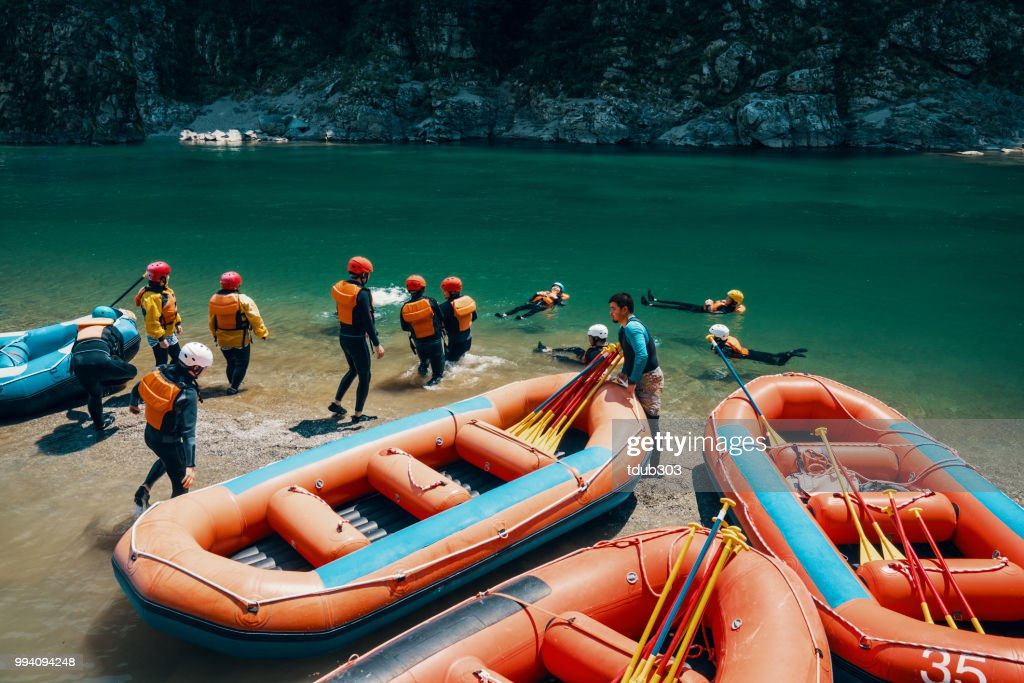 Group of men and women preparing to go white water river rafting : Stock Photo