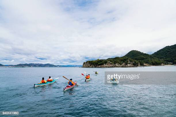 A group of men and women sea kayaking
