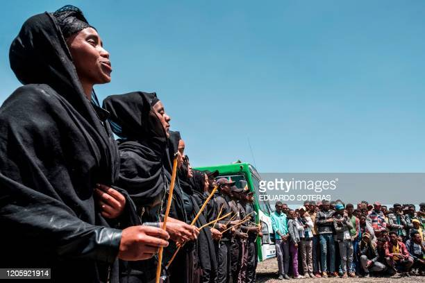 A group of men and women sing during a memorial ceremony at the crash site of the Ethiopian Airlines Flight 302 airplane accident in Tulu Fara...