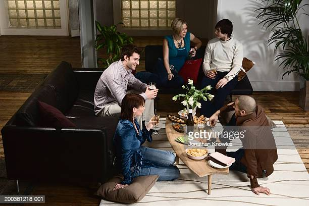 Group of men and women socializing in lounge, finger-food on table