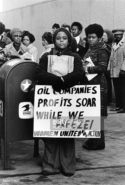 A group of men and women stand with a crowd protesting proposed increase in gas prices Chicago Illinois 1972 One woman holds a sign that reads 'Oil...