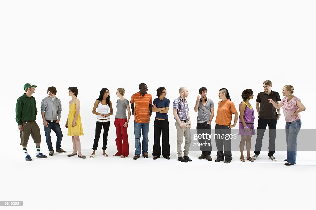 Group of men and women standing in a row and talking : Foto de stock
