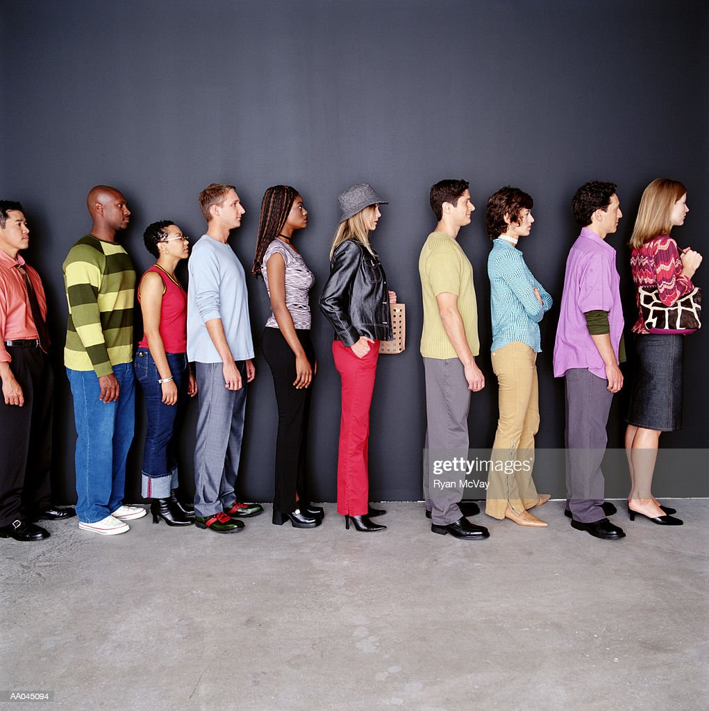 Group of men and women waiting in line, side view : Stock Photo