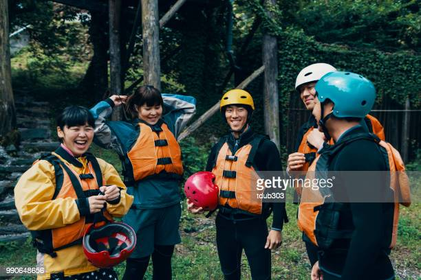Gruppe von Männern und Frauen das Tragen von Schwimmwesten und Helme vor einer River-rafting tour