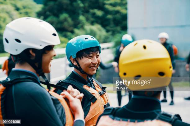 Group of men and women wearing life jackets and helmets before a river rafting tour