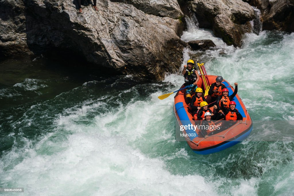 Group of men and women white water river rafting : Stock Photo