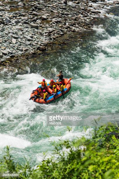 Group of men and women white water river rafting