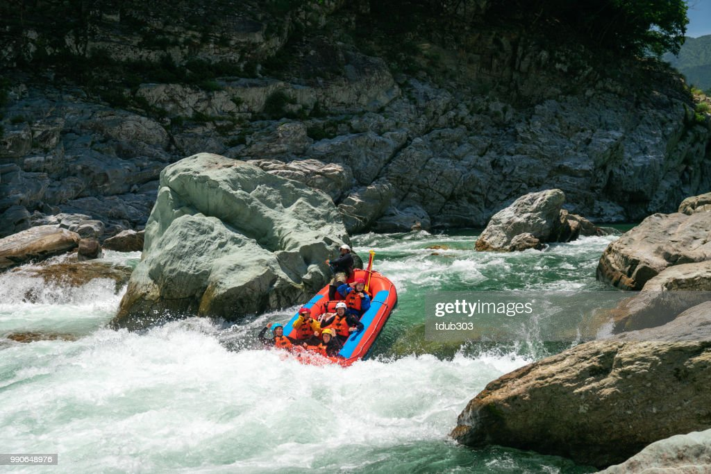Group of men and women white water river rafting : Foto de stock