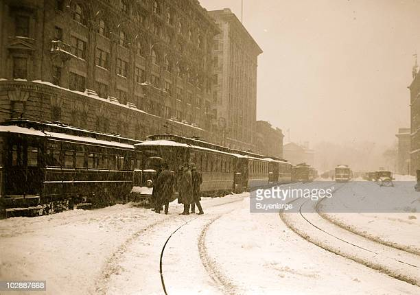A group of men approach a trolley stuck on the rail line while other cars are lined up on the city streets during the Knickerbocker blizzard...