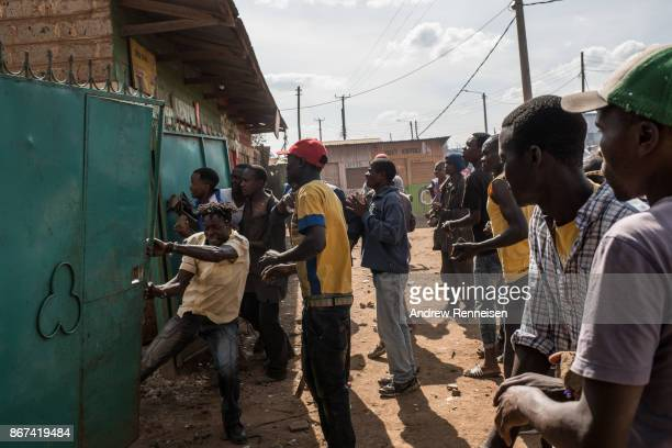 A group of men attempt to open a gate to loot a residential compound in the Kawangware slum on October 28 2017 in Nairobi Kenya Protests continued in...