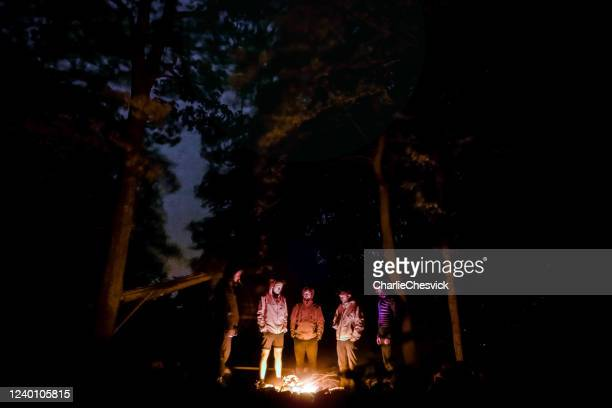 group of men, backpackers, tourist standing around campfire in forest under oak trees and sky is visible between trees white carpathians in czechia (carpathian mountain range) - adults only stock pictures, royalty-free photos & images