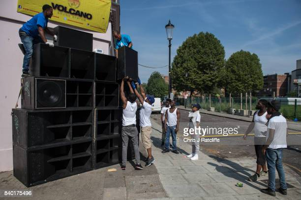 A group of men build a tower of speakers on a street corner for their soundsystem at the Notting Hill Carnival on August 28 2017 in London England...