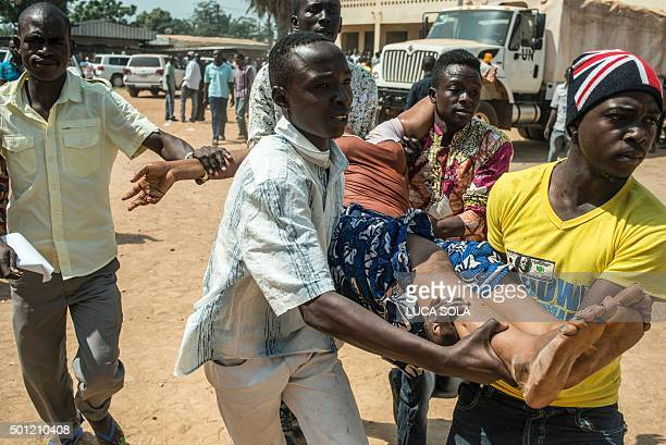 TOPSHOT A group of men carry a woman who passed out as heavy gunfire is directed towards the Baya Dombia school where voters were gathered for the...